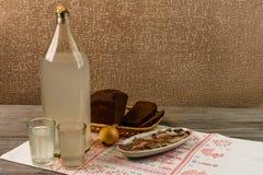 乌克兰全国饮料和快餐 月光大瓶和玻璃在老木桌上的 库存照片