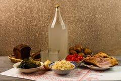 乌克兰全国饮料和快餐 月光大瓶和玻璃在老木桌上的 免版税库存照片