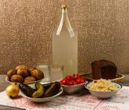 乌克兰全国饮料和快餐 月光大瓶和玻璃在老木桌上的 免版税库存图片