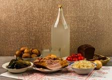 乌克兰全国饮料和快餐 月光大瓶和玻璃在老木桌上的 库存图片