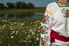 乌克兰刺绣的一个女孩与在她的头的一个花圈由湖在花中的一个草甸 免版税库存图片