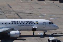 乌克兰国际航空公司乘出租车对跑道的巴西航空工业公司erj190在维也纳机场 库存照片