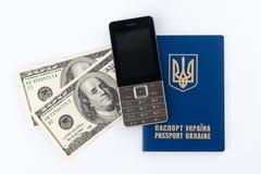 乌克兰在白色bac和手机隔绝的护照、金钱 免版税库存照片