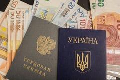 乌克兰护照和俄国作业簿以欧洲票据为背景 免版税库存照片