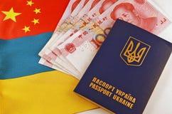 乌克兰护照和元在旗子乌克兰和中国背景  免版税库存图片