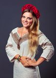 乌克兰服装的年轻俏丽的微笑的女孩有一个红色花圈的 免版税库存图片