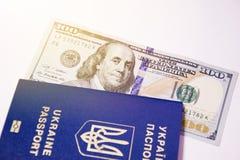 乌克兰生物统计的护照和一一百美元在阳光下 免版税库存照片