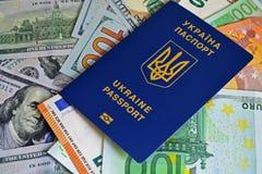 乌克兰生物统计的护照在纸欧洲票据和美元 概念:薪金,乌克兰人增量出国运作 免版税库存图片