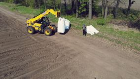 乌克兰,切尔卡瑟州,2019年5月5日:航测,装载者给机械化的机器的拖拉机带来大大袋土豆 股票录像