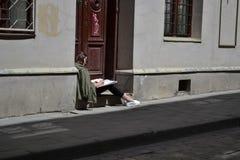 乌克兰,利沃夫州7月30,2015 :一个女孩做剪影城市坐Wirmen街道 免版税库存照片