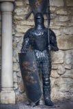 乌克兰,利沃夫州- 2018年10月4日 授以爵位在有剑的充分的装甲以古老墙壁为背景 库存图片