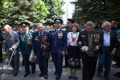 乌克兰,基辅, 2016年5月9日,胜利天, 5月9日 对一个无名战士的纪念碑:二战的退伍军人运载花对monu 库存照片