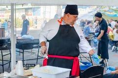乌克兰9月16日2017年,白色教会 一条黑围裙的一位肥胖人厨师准备在街道上的食物 免版税库存照片