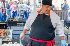 乌克兰9月16日2017年,白色教会 一条黑围裙的一位肥胖人厨师准备在街道上的食物 库存图片