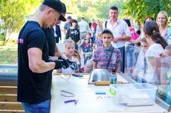乌克兰9月16日2017年,白色教会 孩子观看焦糖的过程烹调户外 免版税库存图片