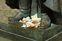 乌克兰hryvnas钞票堆离开在古铜色雕象的脚由运气的turists 免版税库存照片
