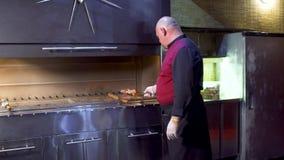 乌兹别克人餐馆的厨师在格栅的串上把生肉放在厨房 影视素材