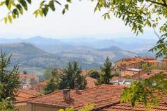 乌尔比诺,意大利- 2017年8月9日:老城市 房子屋顶在红色瓦片下的 在视图之上 库存照片