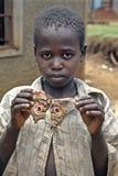 乌干达男孩骄傲地摆在与五颜六色的飞蛾 免版税库存照片
