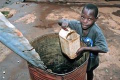 乌干达男孩从接雨水的桶得到饮用水 库存图片
