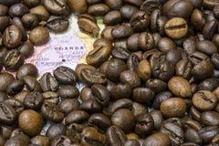 乌干达的地图在咖啡豆下背景的  免版税库存照片