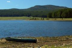 乌拉尔山脉、湖和一条老小船 免版税库存图片