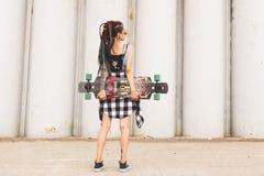 乌法,俄罗斯- 2018 9月12日,女孩社论照片有一longboard的在混凝土结构背景  库存图片