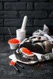 乌贼墨水面包和红色鱼子酱在黑背景 库存图片