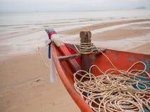 乌贼渔船小船头特写镜头有绳索的在海滩在多云早晨天 免版税图库摄影