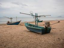乌贼渔船很多在海滩的在多云早晨天,有海背景 免版税库存图片