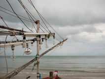 乌贼渔船电灯泡在海滩的在多云早晨天 免版税库存照片