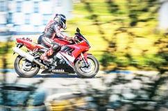 乌里扬诺夫斯克,俄罗斯- 2017年8月19日 与一名未认出的移动的摩托车骑士的抽象bluring的背景山叶的 免版税库存照片