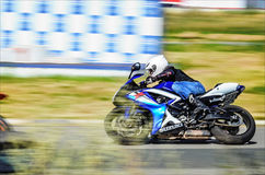 乌里扬诺夫斯克,俄罗斯- 2017年8月19日 有背包的一位摩托车竟赛者在体育轨道的一辆摩托车训练 铃木 库存图片
