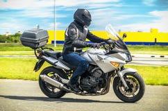 乌里扬诺夫斯克,俄罗斯- 2017年6月10日 一件黑盔甲的一位摩托车竟赛者与背包在有路的一辆摩托车训练 库存图片
