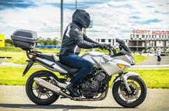 乌里扬诺夫斯克,俄罗斯- 2017年6月10日 一件黑盔甲的一位摩托车竟赛者与背包在有路的一辆摩托车训练 免版税库存照片