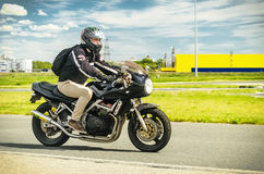 乌里扬诺夫斯克,俄罗斯- 2017年6月10日 一件黑盔甲的一位摩托车竟赛者与背包在a的一辆摩托车训练 免版税库存图片