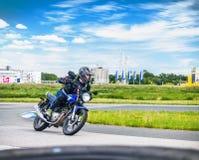 乌里扬诺夫斯克,俄罗斯- 2017年6月10日 黑夹克种族的女孩在体育轨道的一辆蓝色摩托车 图库摄影