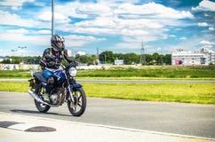 乌里扬诺夫斯克,俄罗斯- 2017年6月10日 黑夹克种族的女孩在体育轨道的一辆蓝色摩托车 免版税库存照片
