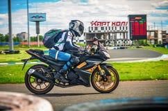 乌里扬诺夫斯克,俄罗斯- 2017年6月10日 有背包的一位摩托车竟赛者在体育轨道的一辆摩托车训练 行动 库存照片
