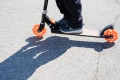 乌里杨诺夫斯克号,俄罗斯- 2019年4月20日:孩子在车行道危险地乘坐滑行车 乘坐的滑行车 公路安全 不安全pede 库存照片
