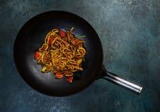 乌龙面混乱与鸡和菜的油炸物面条在葡萄酒的铁锅平底锅上色了背景 顶视图 免版税库存图片