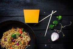 乌龙面混乱与鸡和菜的油炸物面条在黑木背景的铁锅平底锅 使用面条的一个箱子 免版税库存照片