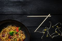乌龙面混乱与鸡和菜的油炸物面条在黑木背景的铁锅平底锅 筷子 免版税图库摄影