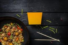 乌龙面混乱油炸物面条用海鲜和菜在铁锅平底锅在黑木背景 使用面条的一个箱子 免版税图库摄影
