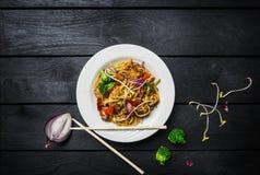 乌龙面混乱油炸物面条用肉或鸡和菜在一块白色板材有筷子的 免版税图库摄影