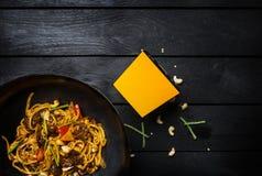 乌龙面混乱油炸物面条用肉或鸡和菜在铁锅平底锅 使用面条的一个箱子 免版税库存照片