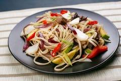 乌龙面铁锅面条用猪肉和胡椒,供食在黑色的盘子, c 库存照片