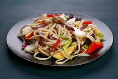 乌龙面铁锅面条用猪肉和胡椒,供食在黑色的盘子, c 免版税库存照片