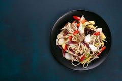 乌龙面铁锅面条用猪肉和胡椒,供食在黑色的盘子, f 免版税图库摄影