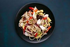 乌龙面铁锅面条用猪肉和胡椒,供食在黑色的盘子, f 免版税库存图片